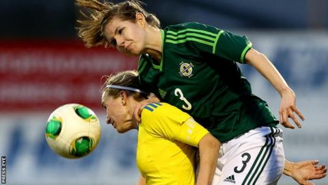 Sweden's Kosovare Asllani is beaten to the high ball by Lisa Armour