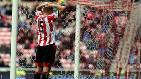 Wes Brown stands dejected after scoring his own goal