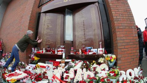 A fan looks for a name on the Hillsborough memorial at Anfield