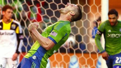 Seattle Sounders midfielder Kenny Cooper celebrates after scoring