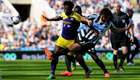 Wilfried Bony of Swansea City is tackled by Fabrizio Coloccini of Newcastle United