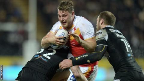 Elliott Whitehead of Catalan Dragons (centre) is tackled by Jordan Rankin and Richard Whiting of Hull FC