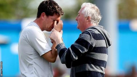 Bristol Rovers manager Darrell Clarke comforted by a fan