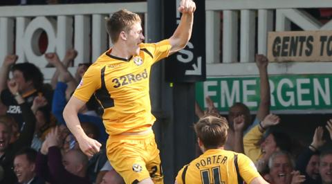Kevin Feely jumps high to celebrate his late winning goal for Newport County against Rochdale at Rodney Parade