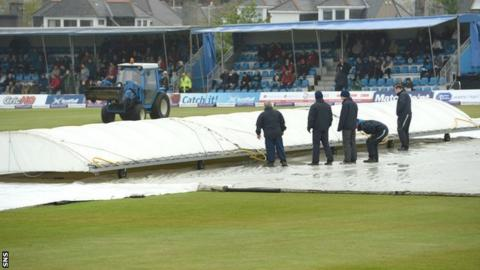 Groundsmen work to protect the pitch at Mannofield