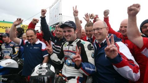 Michael Dunlop celebrates with his team after winning the feature Superbike race following a Superstock victory earlier in the day