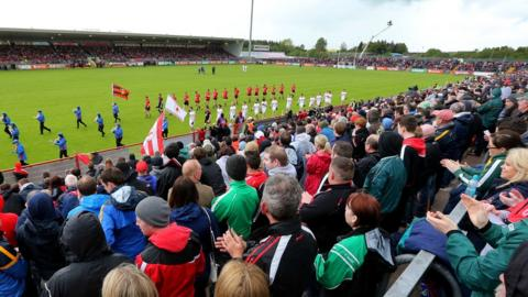The two teams walk out onto a damp Healy Park for the opening match in the 2014 Ulster Senior Football Championship