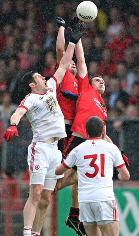 The rain falls at Healy Park as Tyrone captain Sean Cavanagh contests the high ball with Down pair Damien Turley and Declan Rooney