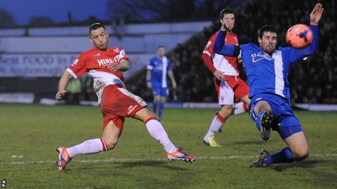 Kidderminster Harriers' Lee Vaughan (left) has a shot on goal against Peterborough United.
