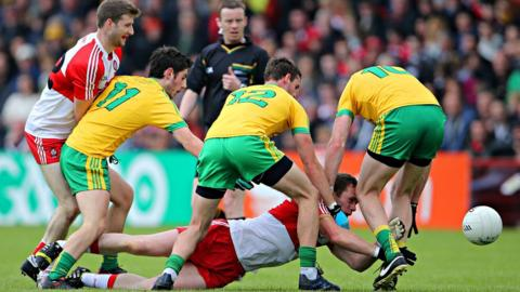Derry's Patsy Bradley hits the deck as Donegal opponents Ryan McHugh, Odhran MacNiallais and Christy Toye attempt to win possession