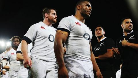 England's Ben Morgan and Kyle Eastmond look dejected as New Zealand's Liam Messam enjoys the victory