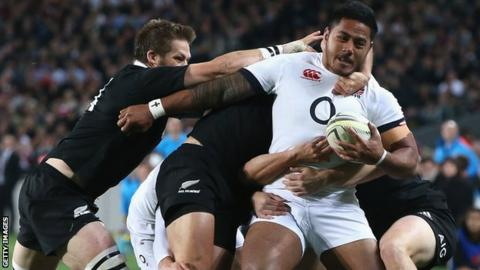 Manu Tuilagi of England is tackled by the All Black defence