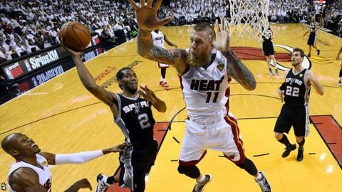 San Antonio Spurs forward Kawhi Leonard goes to the basket under pressure from Miami Heat forward Chris Andersen