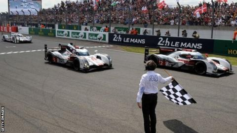 Audi team crosses the finish line to take the chequered flag in its 379th and last lap to win the 82nd Le Mans 24 Hour Race