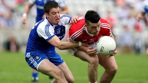 Gerard McCaffrey of Monaghan attempts to dispossess Tyrone's Darren McCurry during the Ulster Championship quarter-final at Clones