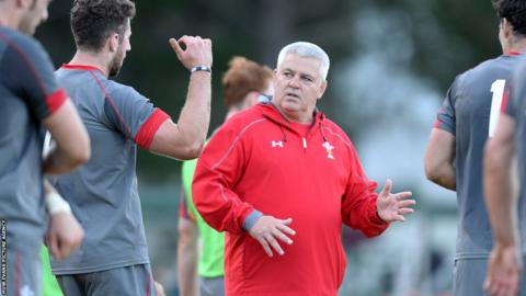 Wales coach Warren Gatland discusses tactics with wing Alex Cuthbert during training.