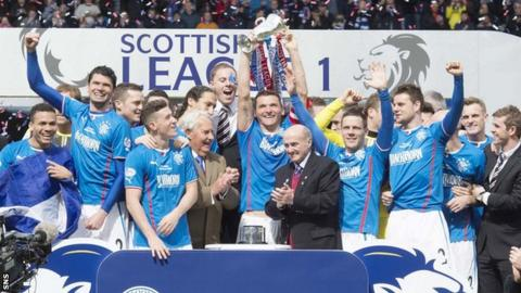 Rangers players celebrate with the Scottish League One trophy
