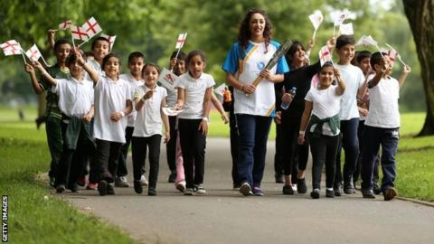 Mimi Cesar carries the Queen's Baton through Ward End Park, Birmingham, June 2014