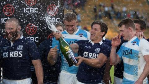 Scotland's scrum-half Grayson Hart (2R) spray champagne after the victory over Argentina in Cordoba