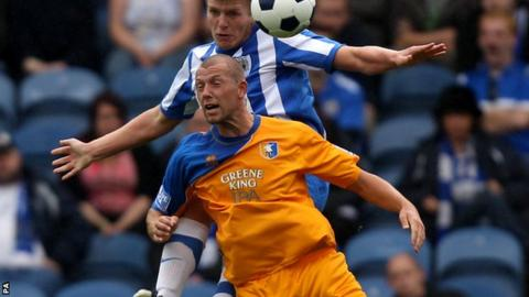 Stockport County's Carl Piergianni and Mansfield Town's Ross Dyer battle for possession of the ball in the air