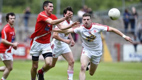 Louth's Ryan Burns delivers his pass despite close attention from PJ Quinn in Tyrone's 2-21 to 0-10 victory