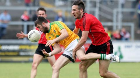 Leitrim's Kevin Conlan loses control of the ball thanks to pressure from Dan Gordon as Down cruised to a 4-18 to 0-9 success