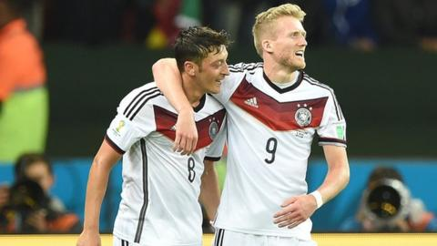 Mesut Ozil and Andre Schurrle celebrate as Germany beat Algeria 2-1