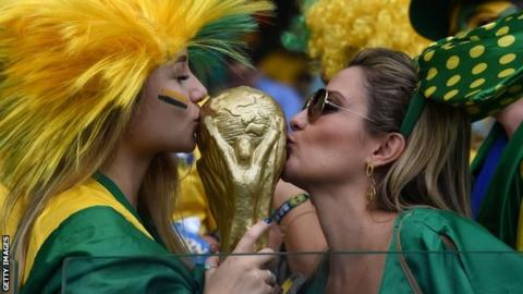 Two Brazil fans kiss a replica World Cup trophy