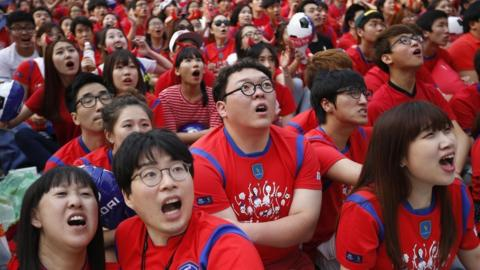 South Korean soccer fans react as they watch a live TV broadcast of their 2014 World Cup Group H soccer match against Russia in Seoul