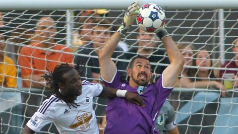 New Swansea City striker Bafetimbi Gomis challenges the Minnesota United goalkeeper for the ball