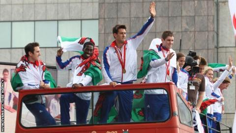 Welsh Olympic athletes wave to the crowds in Cardiff from the top of an open top bus.