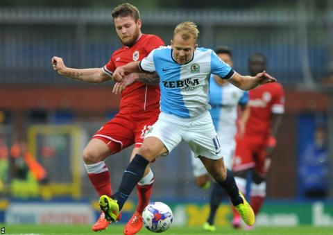 Cardiff City midfielder Aron Gunnarsson battles for the ball with Blackburn Rovers striker Jordan Rhodes at Ewood Park