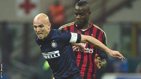 Inter Milan's Esteban Cambiasso (left) holds off AC Milan's Mario Balotelli