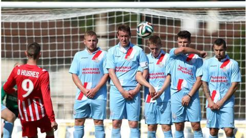 Daniel Hughes of Warrenpoint Town attempts to beat Ballymena United's defensive wall during the Premiership match at the Showgrounds