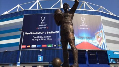 The Fred Keenor statue outside the Cardiff City stadium in front of the banner for the Uefa Super Cup.