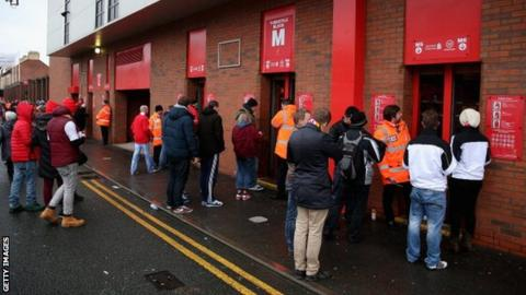 Fans queue at a turnstile