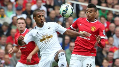 Swansea City's Wayne Routledge battles for the ball with Manchester United's Jesse Lingard.