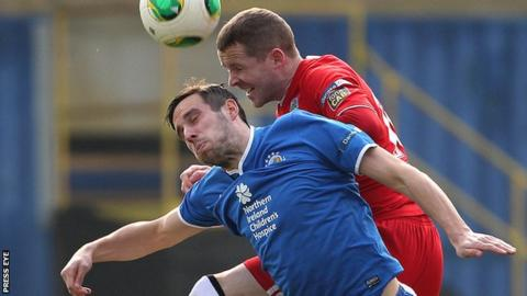 Linfield's Andy Waterworth is btaen to the high ball by Cliftonville defender Marc Smyth
