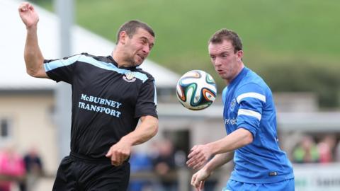 Ballymena United striker Matthew Tipton in action against David Kee of Ballinamallard United at Ferney Park