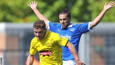 Alex MacDonald (left) challenged by Portsmouth's Ricky Holmes