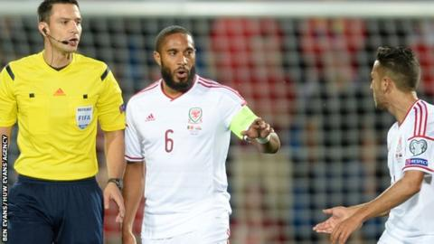 Ashley Williams and Neil Taylor talk to Referee Slavko Vincic following the Andorra penalty