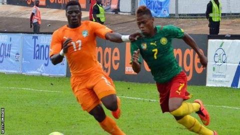 Ivory Coast's Serge Aurier and Cameroon's Clinton Njie vie for the ball