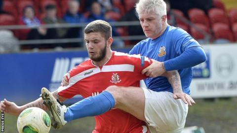 William Murphy gets his foot in ahead of Portadown striker Darren Murray