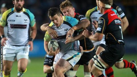 Aaron Jarvis of Ospreys is tackled by Lewis Evans