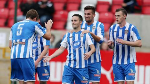 Coleraine players surround Neil McCafferty after he scores the winning goal against Cliftonville at Solitude