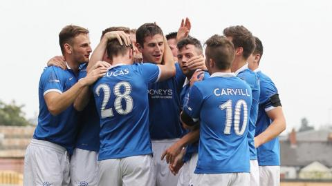 Linfield players converge to congratulate Mark Haughey after the defender scored what proved to be the Blues' winning goal