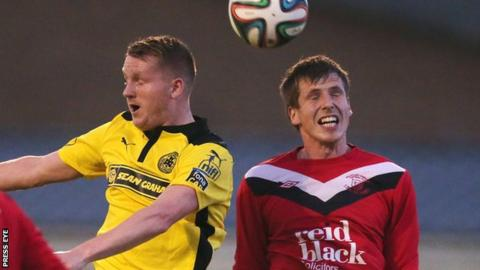 Cliftonville midfielder Martin Murray contests a high ball with Ballyclare's Randal Reid