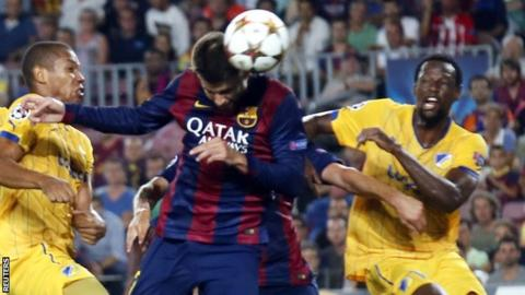 Barcelona defender Gerard Pique heads his team ahead against Apoel Nicosia in the Champions League