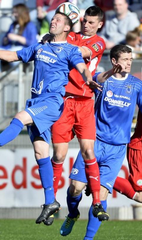 Dungannon Swifts defender Terry Fitzpatrick and Cliftonville's Johnny Flynn contest a high ball in the Solitude encounter