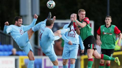 Institute's Aaron Walsh gets his boot to the ball ahead of Glentoran opponent Calum Birney at Drumahoe